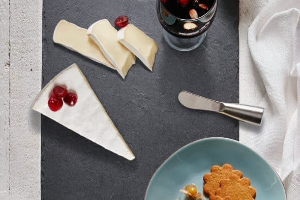 Sliced brie placed alomg side a glass of glogg and some gingerbread cookies