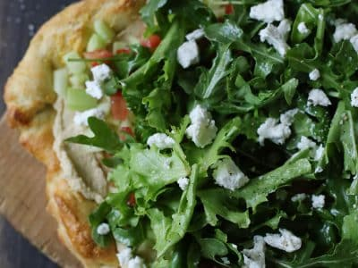 Pizza topped with fresh salad, fruit and cheese