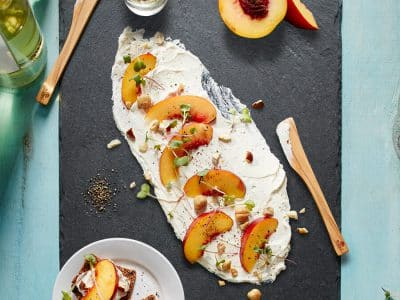 Cheese spread on the cheeseboard and topped with nectarines and hazelnuts